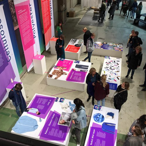 Large coloured posters and low tables with posters and objects