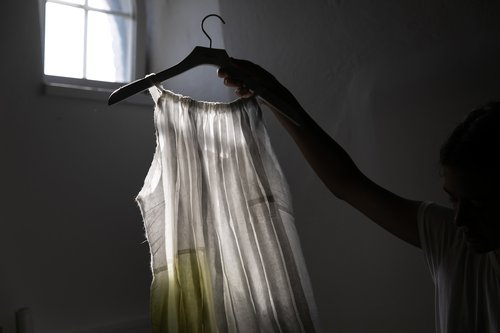 A dress on a coat hanger being help up to light coming in from a window