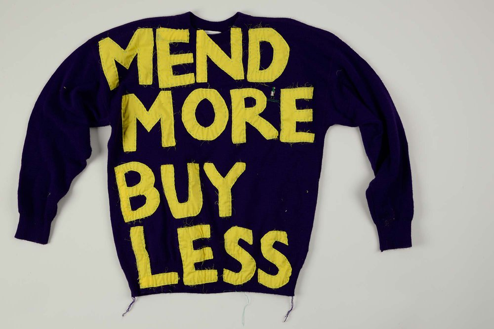A black jumper with the words 'Mend more buy less' written on it
