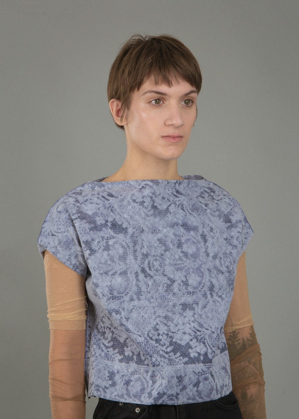 A woman wearing a shirt with a laser cut floral pattern