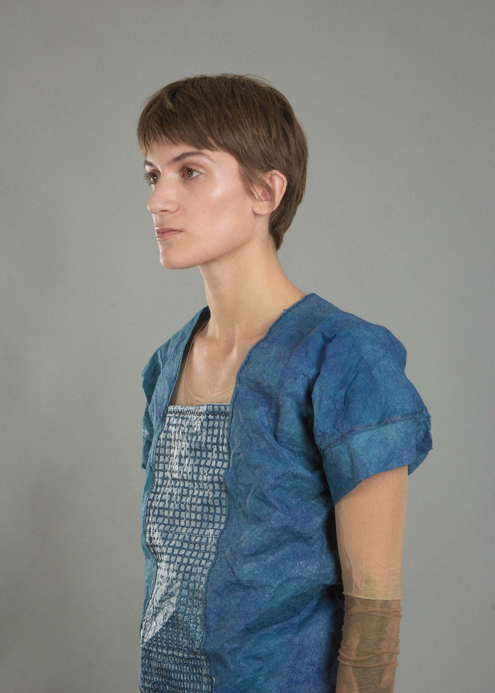 A women wearing a blue shirt with a laser cut pattern down the middle