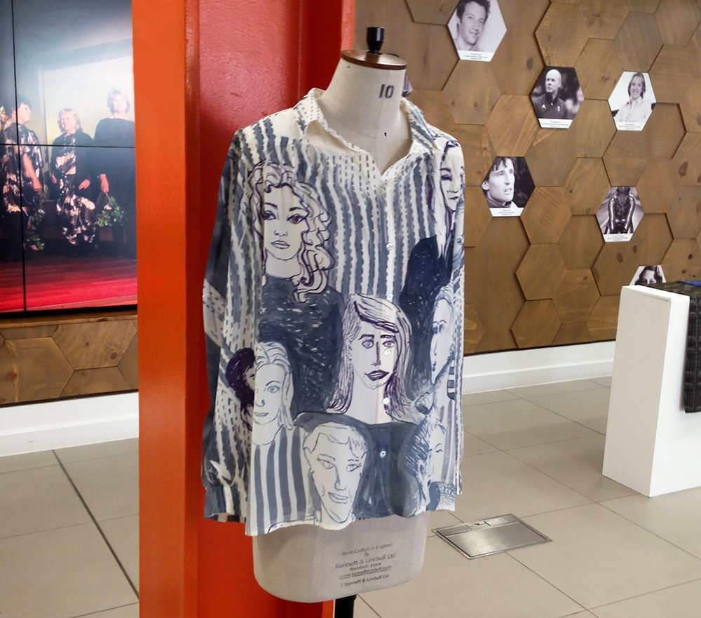 A shirt of illustrated potraits on a mannequin against a red metal post.