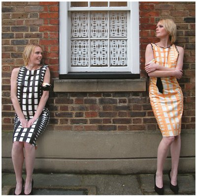 Two women standing either side of a window wearing dresses with a  bold rectangular print.
