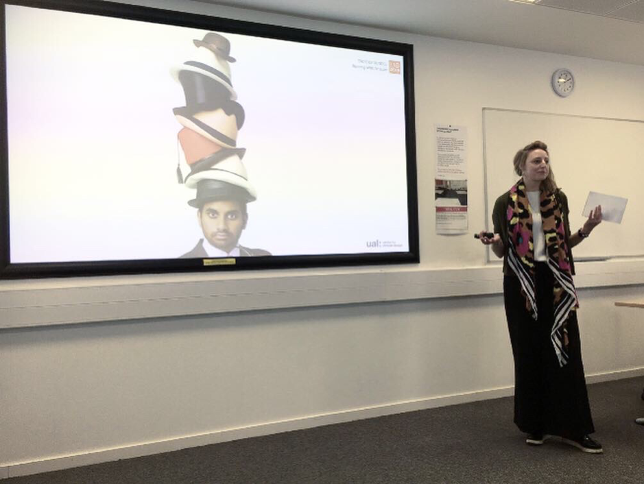 Cathryn Hall in front of a projector screen which shows a man wearing a pile of hats.