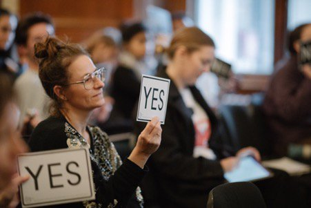 A woman holding a card saying 'yes'